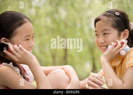 Two girls talking on their mobile phones and smiling - Stock Photo
