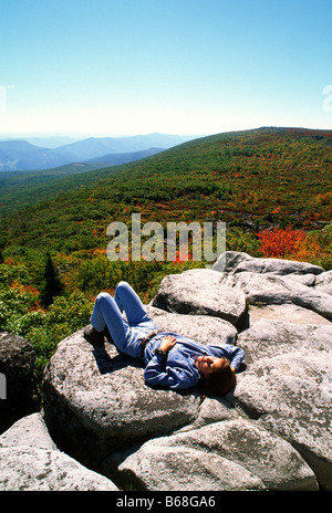 A woman enjoys resting in the sunshine on a mountain overlook Dolly Sods West Virginia - Stock Photo