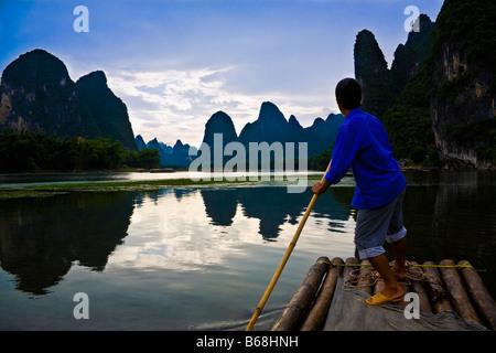 Side profile of a mature man rowing a wooden raft in a river, Li River, XingPing, Yangshuo, Guangxi Province, China - Stock Photo