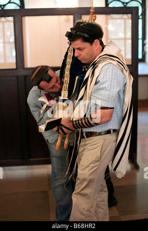 One man kisses the Torah as another carries it during services in the Nozyk Synagogue in Warsaw. - Stock Photo
