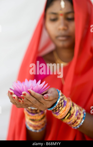 Indian woman offering a Nymphaea Tropical waterlily flower in a red sari. Andhra Pradesh, India - Stock Photo