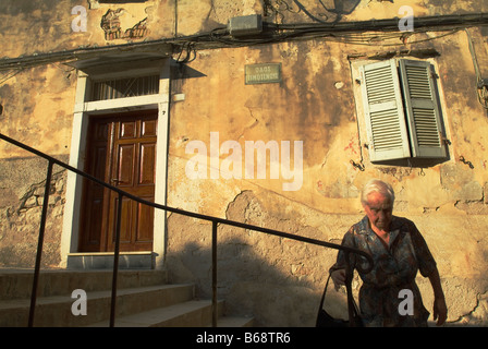 Local Woman walking in the 'Old Town' Corfu, Greece - Stock Photo