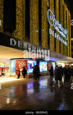 Debenhams department store Oxford street with Christmas lights in Londons West End rainy evening - Stock Photo