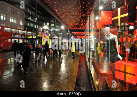 Shoppers on wet pavement outside department store front windows with Xmas gifts on display Oxford Street Christmas - Stock Photo