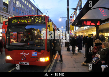 Oxford street bus stop bendy bus with electronic timetable bus driver Christmas shoppers - Stock Photo
