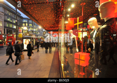 Shoppers on pavement outside department store front windows with Xmas gifts on display at Oxford Street with Christmas - Stock Photo