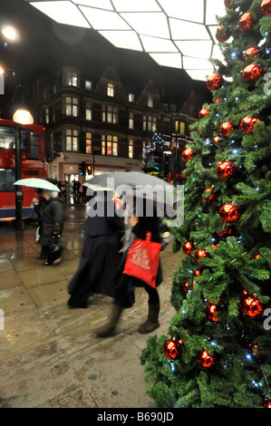 Christmas shoppers in Oxford street under umbrellas outside main entrance to Selfridges department store on a rainy - Stock Photo