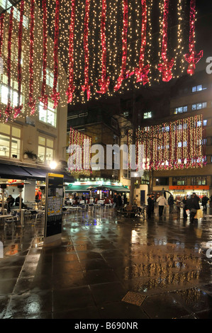 Christmas lights in St Christophers Place shopping & eating out area off Oxford Street in Londons West End rainy - Stock Photo