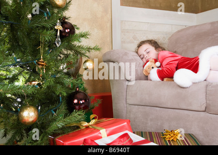 Girl (6-7) sleeping on sofa by Christmas tree - Stock Photo