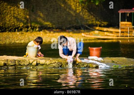 Young woman with her daughter washing clothes at a riverside, Li River, XingPing, Yangshuo, Guangxi Province, China - Stock Photo