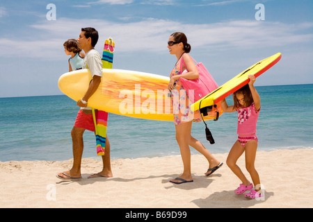 Couple with their children walking on the beach - Stock Photo