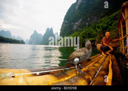 Fisherman on a bamboo raft, Guilin Hills, XingPing, Yangshuo, Guangxi Province, China - Stock Photo