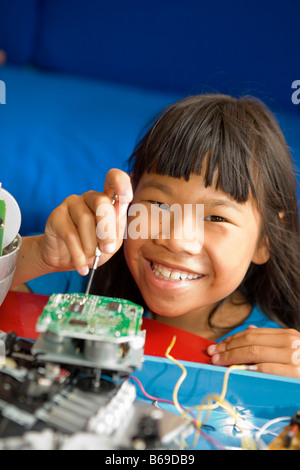 Portrait of a girl repairing a radio - Stock Photo