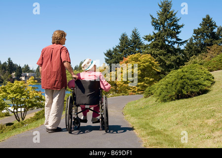 Man assisting his disabled mother in a wheelchair - Stock Photo