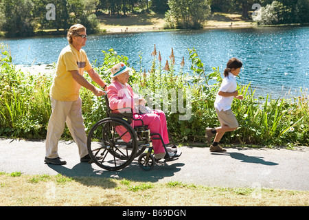 Man pushing his mother sitting in a wheelchair - Stock Photo