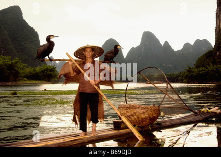 Senior man on a bamboo raft with a hill range in the background, Guilin Hills, XingPing, Yangshuo, Guangxi Province, - Stock Photo