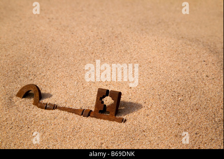 A rusty old key buried in the sand - Stock Photo
