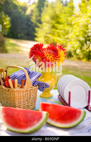 Two watermelon slices with a basket and a vase of flowers on a table - Stock Photo
