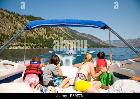 Family in a motorboat and looking at a person waterskiing, Lake Chelan, Washington State, USA - Stock Photo
