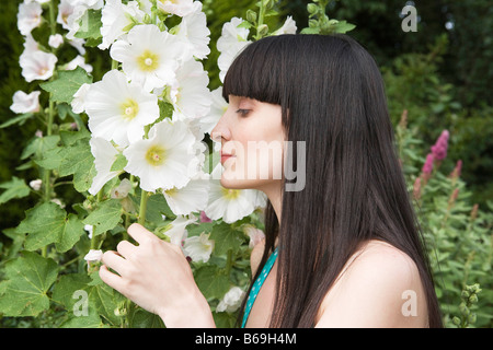 Woman smelling flowers in garden - Stock Photo