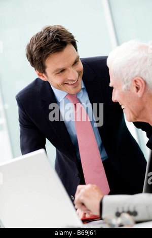 Younger man talking to older man - Stock Photo