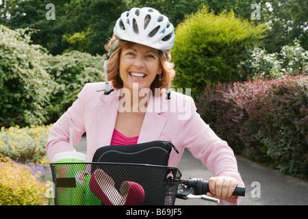 Woman wearing helmet on bicycle - Stock Photo