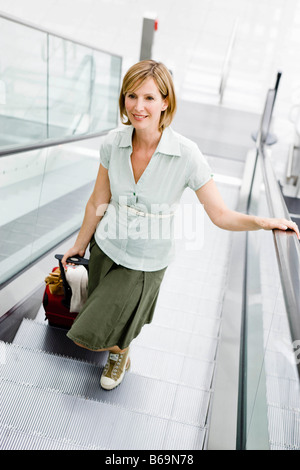 Woman walking an escalator - Stock Photo