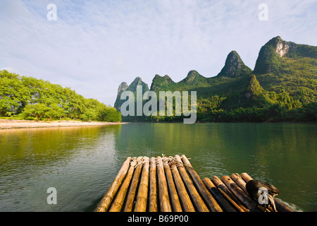 Bamboo raft in a river with a hill range in the background, Guilin Hills, XingPing, Yangshuo, Guangxi Province, - Stock Photo
