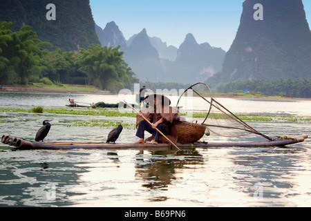 Fisherman fishing in a river with a hill range in the background, Guilin Hills, XingPing, Yangshuo, Guangxi Province, - Stock Photo