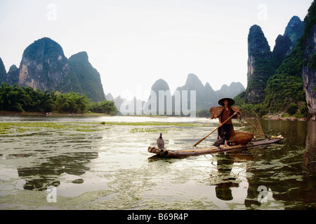 Fisherman on a bamboo raft with a hill range in the background, Guilin Hills, XingPing, Yangshuo, Guangxi Province, - Stock Photo
