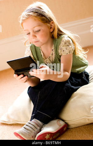 little girl playing a handheld computer game - Stock Photo