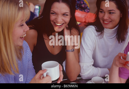 three women chatting over a coffee - Stock Photo