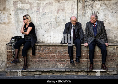 Two elderly Italian men have a conversation while a younger woman talks on her mobile phone in Siena, Italy - Stock Photo