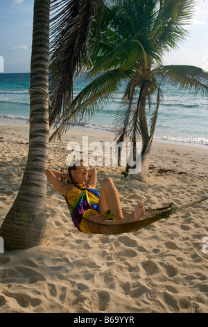 Mexico, Quintana Roo, Tulum, Tourist (woman) in hammock under palm trees at beach - Stock Photo