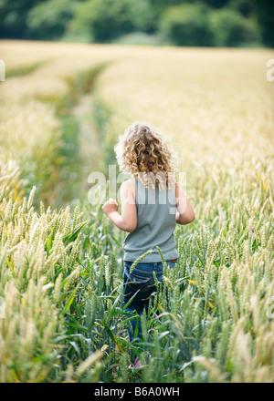 Young girl walking path in cornfield - Stock Photo