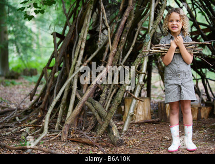 Young girl with pile of twigs in woods - Stock Photo
