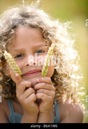 Young girl holds up ears of corn - Stock Photo