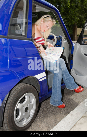 Young woman reading map in electric car - Stock Photo