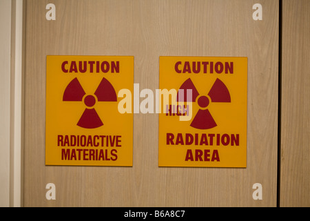 Caution radioactive area pair of signs on a door in a medical building - Stock Photo