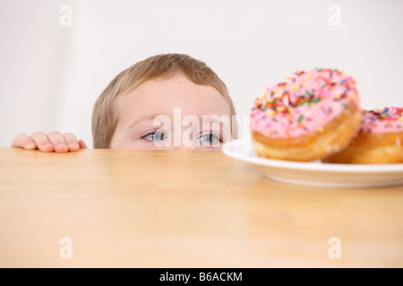 Young boy peeking over table at plate of doughnuts - Stock Photo