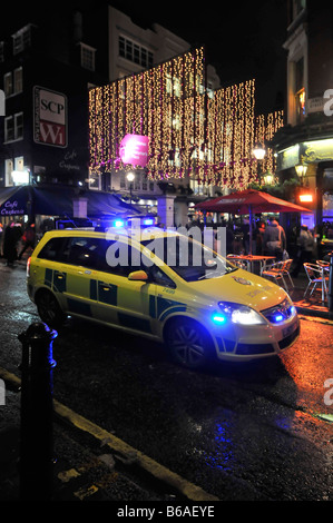 London West End ambulance car on emergency 999 call stuck in rush hour traffic blue lights at Christmas time - Stock Photo