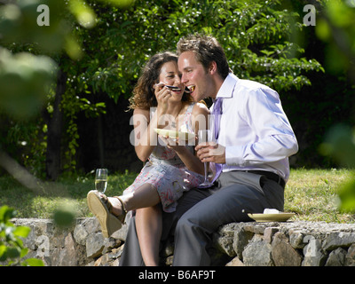 Wedding guests eating cake - Stock Photo