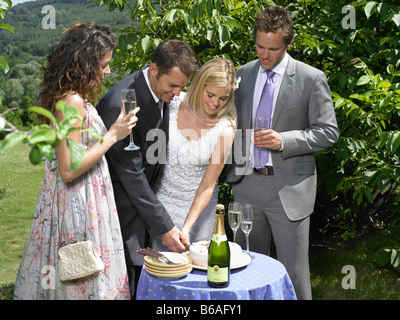 Bride and groom cutting cake - Stock Photo