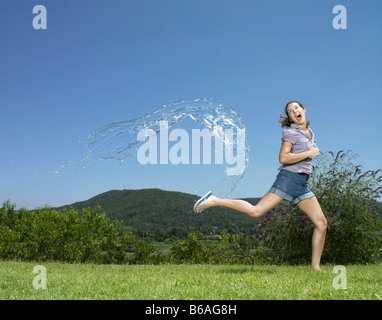 Girl running from arc of water - Stock Photo