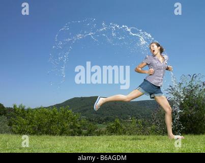 Girl running through arc of water - Stock Photo