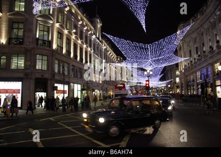 London taxi passing under Christmas lights i Regents Street London UK - Stock Photo