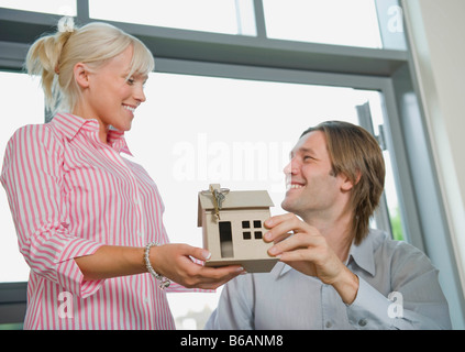 Couple holding a model of a house - Stock Photo
