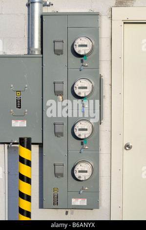 4 four [electric meters] mounted on exterior of building,USA - Stock Photo