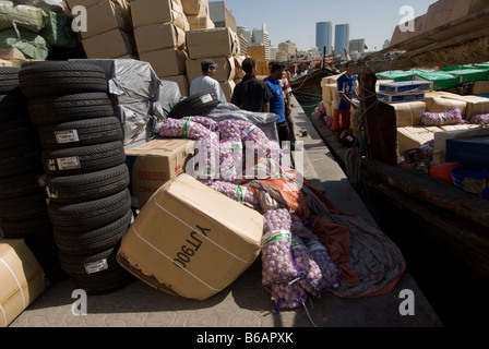 A wide variety of goods await loading on a small ship in Dubai creek before shipping to Iran despite international - Stock Photo