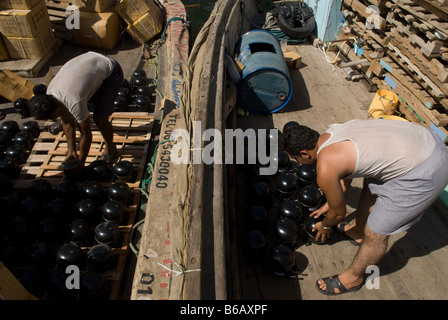 A worker in Dubai Creek loading small engines on a ship which will leave for Iran that same night despite international - Stock Photo